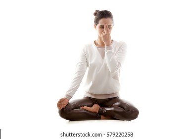 Young attractive woman practicing yoga, doing Alternate Nostril Breathing, nadi shodhana pranayama exercise, Sukhasana pose, working out in casual wear, full length, isolated, white background