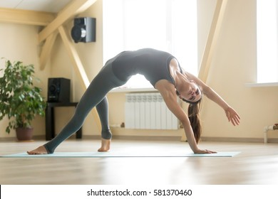 Young attractive woman practicing yoga, doing Wild Thing, Flip-the-Dog exercise, Camatkarasana pose, working out, wearing grey sportswear, indoor full length, home interior or sport club background