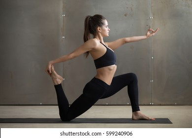 Young attractive woman practicing yoga, standing in Horse rider exercise, anjaneyasana pose, working out, wearing black sportswear, cool urban style, full length, grey studio background, side view