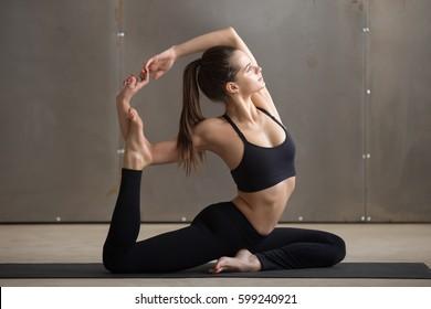 Young attractive woman practicing yoga, sitting in Mermaid exercise, Eka Pada Rajakapotasana pose, working out, wearing black sportswear, cool urban style, full length, grey studio background