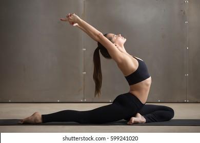 Young attractive woman practicing yoga, stretching in One Legged King Pigeon exercise, Eka Pada Raja Kapotasana pose, working out, wearing black sportswear, cool urban style, full length, grey studio