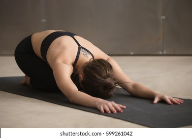 Young attractive woman practicing yoga, stretching in Child exercise, Balasana pose, working out, wearing black sportswear, cool urban style, full length, grey studio background
