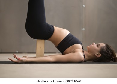 Young attractive woman practicing yoga, standing in Viparita Karani exercise, using wooden block, working out, wearing black sportswear, cool urban style, grey studio background, closeup, side view