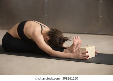 Young attractive woman practicing yoga, stretching in paschimottanasana exercise, using wooden block, Seated forward bend pose, wearing sportswear, working out, full length, cool urban style, studio