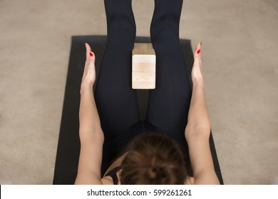 Young attractive woman practicing yoga using wooden block, doing navasana exercise, working out, wearing black sportswear, cool urban style, grey studio floor background, closeup, high angle view