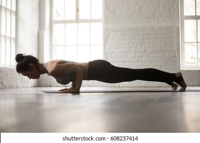 Young attractive woman practicing yoga, standing in chaturanga dandasana exercise, four limbed staff, Push ups or press ups pose, working out, white loft studio background, full length, side view