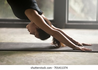 Young attractive woman practicing yoga, stretching in adho mukha svanasana exercise, downward facing dog pose, working out, wearing sportswear, black top, indoor close up, studio background