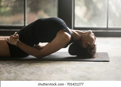Young attractive woman practicing yoga at home, stretching in Fish exercise, Matsyasana pose, working out, wearing sportswear, black shorts and top, indoor close up image, studio background