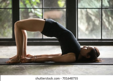 Young attractive woman practicing yoga at home, stretching in Glute Bridge exercise, dvi pada pithasana pose, working out wearing sportswear black shorts and top, indoor full length, studio background