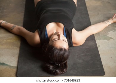 Young attractive woman practicing yoga at home, lying in Savasana exercise, Corpse pose, working out, wearing sportswear, black top, indoor full length, studio floor background