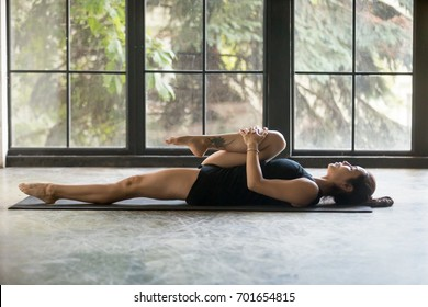 Young attractive woman practicing yoga at home, stretching in Apanasana exercise, Knees to Chest pose, working out, wearing sportswear, black shorts and top, indoor full length, studio background