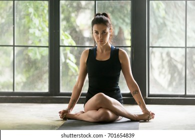 Young attractive woman practicing yoga at home, sitting in Gomukasana exercise, Cow Face pose, working out, wearing sportswear, black shorts and top, indoor full length, window background