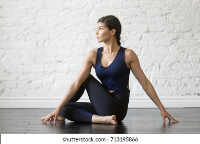 Young attractive woman practicing yoga, sitting in Ardha Matsyendrasana exercise, Half lord of the fishes pose, working out, wearing sportswear, black top, pants, indoor full length, studio background