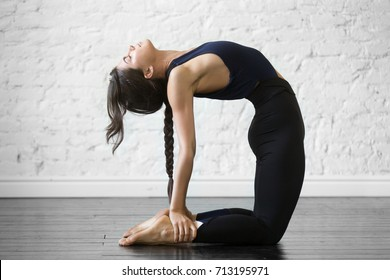 Young attractive woman practicing yoga, stretching in Ustrasana exercise, Camel pose, working out, wearing sportswear, black top and pants, indoor full length, studio background