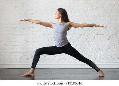 Young attractive woman practicing yoga, standing in Warrior one exercise, Virabhadrasana II pose, working out, wearing sportswear, gray tank top, black pants, indoor full length, studio background
