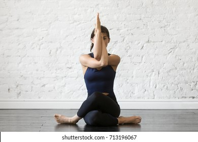Young attractive woman practicing yoga, sitting in Gomukasana exercise, Cow Face pose, working out, wearing sportswear, black top and pants, indoor full length, studio background