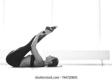 Young attractive woman practicing yoga near window. Black and white.