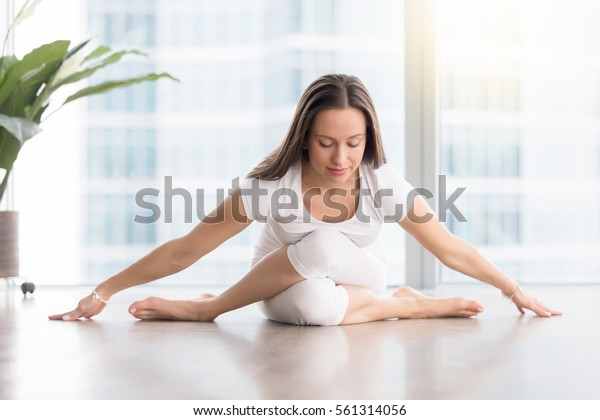 Young attractive woman practicing yoga in apartment, sitting in variation of Gomukasana exercise with forward bend, Cow Face pose, working out, wearing white sportswear, indoor full length