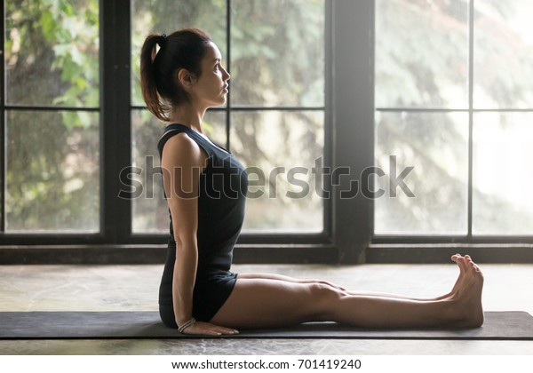 Young attractive woman practicing yoga at home, sitting in Staff exercise, Dandasana pose, working out, wearing sportswear, black shorts and top, indoor full length, studio background