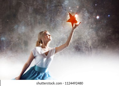 Young attractive woman reaching for the star. Take a star from the sky, dreams and plans, concept. Textured gray background