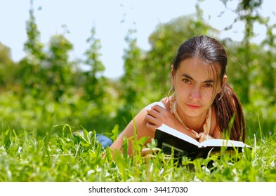 Young attractive woman reading a book and lying on a grass