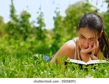 Young attractive woman reading a book lying on a grass