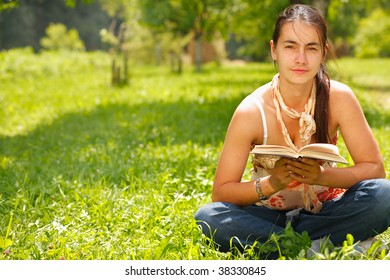 Young attractive woman reading a book and sitting on a grass