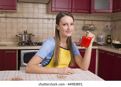 Young attractive woman with red bell peppers in the kitchen