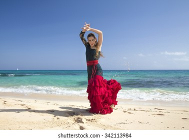 young attractive woman in red and green  flamenco dress by ocean shore