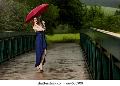 Young attractive woman with red umbrella after rain in nature