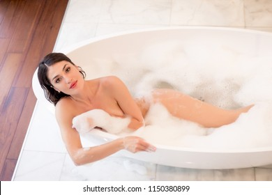 Young attractive woman relaxing in bath with foam - Beautiful girl taking a shower in his apartment