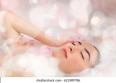 Young attractive woman relaxing in bath with foam and petals, closeup
