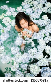 Young attractive woman relaxing in clean outdoor bath with blue hydrangea. Healthy spa treatment with anti-inflammatory and tonic effects. Lifestyle concept.