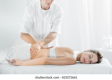 Young and attractive woman relaxing during massage in professional salon