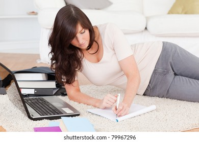 Young attractive woman relaxing with her laptop while writing on a notebook in the living room