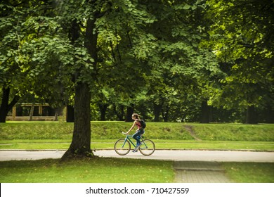 Young attractive woman riding a bicycle through a park with trees on vacation, Sunny day outdoors, Happy smiling beautiful woman riding bikes in bright sunlight on summer day, Age 20-30 years