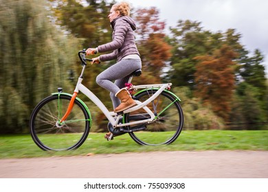 Young attractive woman riding bike in nature. Autumns recreation bicycle day in the park. Adult woman cycling outdoor. Panning, motion.