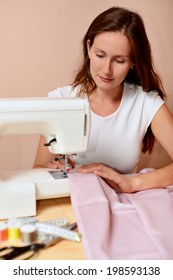 Young attractive woman sewing