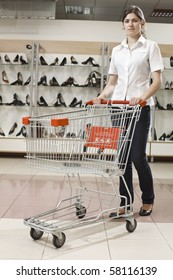 Young attractive woman with a shopping cart in a shoe store