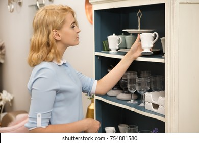Young attractive woman shopping for dinnerware at the local store examining ceramic cup smiling joyfully copyspace home coziness decor buyer shopper shopaholic consumerism retail purchase designer