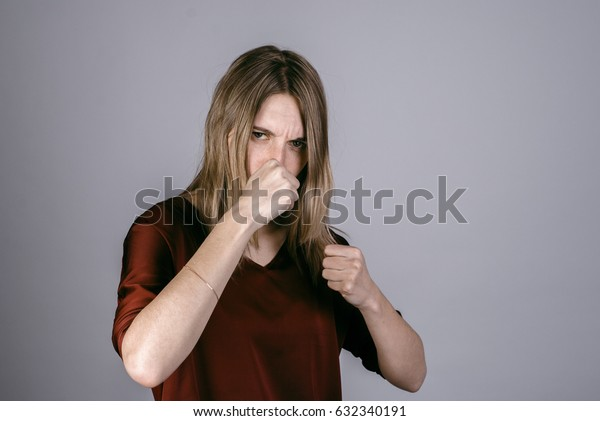 Young attractive woman showing punch gesture. Female with fists.