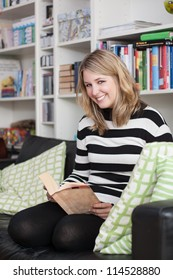 Young, attractive woman sits on the couch and reads a book at home. A bookshelf is at the background.