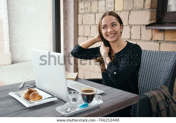 Young attractive woman sitting in a cafe in the morning before her work and planning tasks for the whole day. Beautiful lady talking on the phone and discussing business strategies with her colleague.