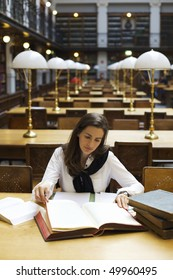 Young attractive woman sitting at desk in old university library studying books, front view.