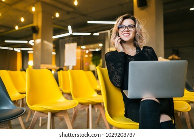 young attractive woman sitting in lecture hall, working on laptop, wearing glasses, many yellow chairs, student education online, freelancer, smiling, talking on smartphone, looking forward, startup