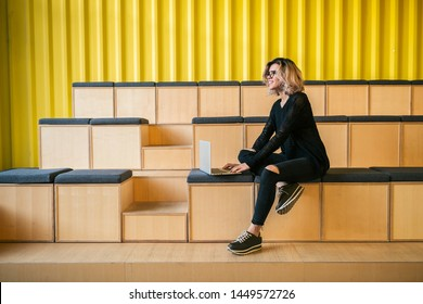 young attractive woman sitting in lecture hall, working on laptop wearing glasses, modern auditorium, student education online