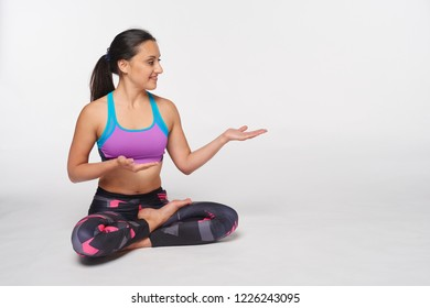 Young attractive woman sitting in lotus pose in full length showing and looking to side at blank copy space, isolated over white studio background