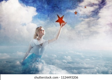 Young attractive woman Sitting on a cloud reaching for the star. Take a star from the sky, dreams and plans, concept. Textured gray background