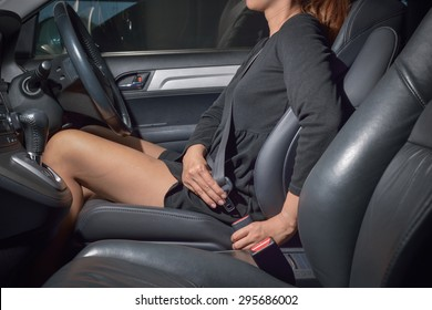 Young attractive woman sitting on car seat and fastening seat belt, car safety concept.