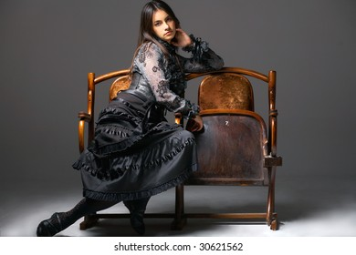 A young attractive woman sitting on old theater armchairs